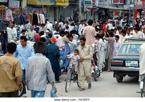 man-wheeling-child-on-bicycle-in-crowded-street-in-islamabad-in-pakistan-ae5dff